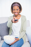 Cheerful cute woman sitting on sofa changing tv channel and holding popcorn