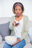 Shocked woman sitting on sofa changing tv channel while holding popcorn