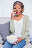 Cheerful attractive woman eating popcorn