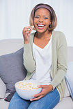 Laughing woman eating popcorn