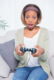 Shocked woman sitting on sofa playing video games
