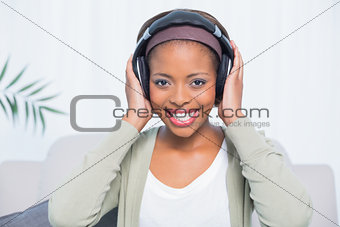 Attractive woman relaxing with headphones while sitting on a sofa