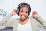 Dancing woman listening to music with headphones while looking at camera