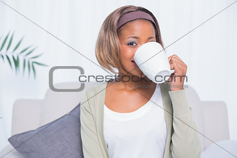 Attractive woman sitting on sofa drinking coffee