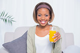 Smiling woman sitting on sofa holding glass of orange juice