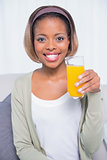 Pretty woman sitting on sofa holding orange juice