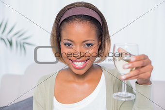 Smiling woman sitting on sofa holding glass of water