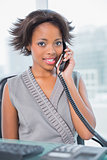 Smiling businesswoman sitting on her desk calling on phone