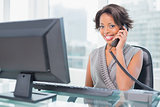 Smiling businesswoman talking on phone while looking at camera