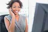 Smiling businesswoman talking on phone while looking at computer screen