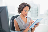 Frowning businesswoman sitting at desk holding tablet pc