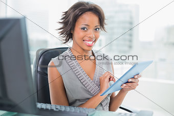 Beautiful businesswoman using her tablet pc and smiling at camera