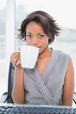 Peaceful businesswoman drinking coffee while having break
