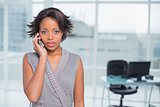 Serious businesswoman standing in her office talking on phone