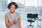 Smiling woman standing in her office and using her phone
