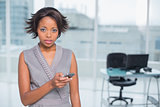Unsmiling businesswoman standing in her office and texting