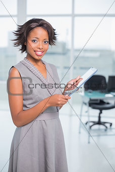 Attractive businesswoman standin in her office holding tablet