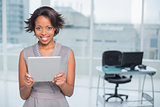 Smiling businesswoman standing in her office and holding tablet