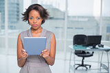 Serious businesswoman standing in her office holding tablet