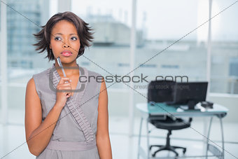 Thoughtful businesswoman standing in her office