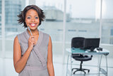Smiling businesswoman standing in her office holding pen