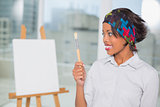 Pretty artist looking at her brush