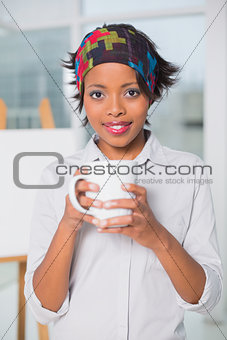 Artistic woman holding cup of coffee