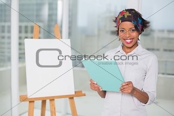 Smiling artistic woman holding sketchpad