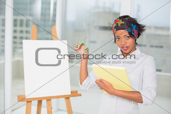Attractive artistic woman holding sketchpad and scissors