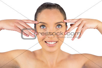 Attractive woman touching her face and looking upwards
