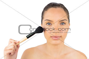 Attractive woman using a powder brush