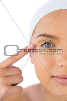 Attractive woman with headband on putting cream on her face