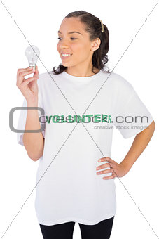 Smiling volunteer woman looking at a light bulb