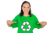 Smiling woman wearing green recycling tshirt pointing on it