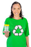 Happy woman wearing green recycling tshirt holding jar