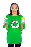 Smiling woman wearing green recycling tshirt holding two glass jars