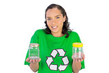 Wondering woman wearing green shirt with recycling sign holding two glass jars
