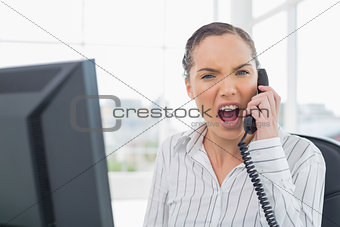 Angry businesswoman screaming on telephone while looking at camera