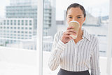 Smiling businesswoman drinking coffee while looking at camera