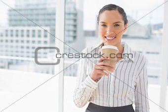 Amused businesswoman holding a coffee