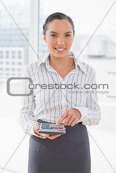 Calm pretty businesswoman using a calculator