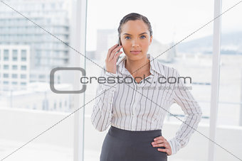 Attractive businesswoman standing in her office and talking on the phone
