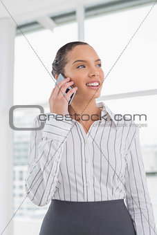 Positive businesswoman standing while talking on phone