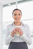 Smiling businesswoman holding a coffee