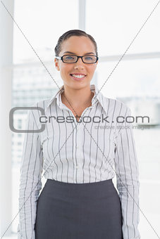 Attractive businesswoman wearing reading glasses standing in her office