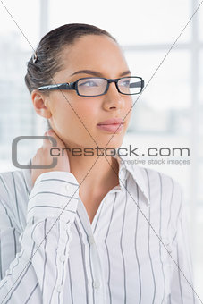 Thoughtful businesswoman with reading glasses standing in office