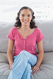 Relaxed woman sitting on sofa and smiling at camera