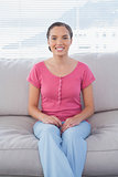 Happy woman sitting on couch and looking at camera