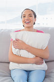 Smiling woman sitting on the sofa hugging a pillow
