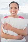 Happy woman sitting on sofa holding pillow
